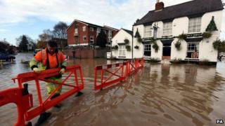 A highways agency worker barriers off the road outside the White Bear Pub in Tewkesbury to stop motorists driving through flood water and flooding the pub further