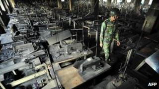 A soldier walks through the site of fire at Tazreen Fashions plant near Dhaka, 26 November 2012