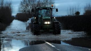A tractor on a flooded road near Moorland, Somerset
