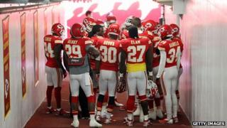 Kansas City Chiefs players huddle in prayer in the tunnel to the field before their game against the Carolina Panthers at Arrowhead Stadium in Kansas City, Missouri, 2 December 2012