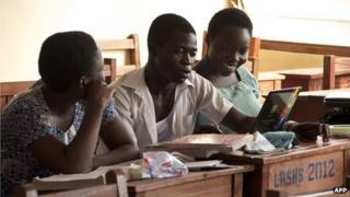 Three Ghanaian pupils - Ernestina Quaye (L), Narteh Andrews (C) and Lisa Okudzetp (R) - sit in a classroom in Accra on 1 December