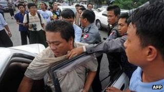 Myanmar police (back R) arrest protester Aung Soe (L) and put him into a car during a protest in Rangoon on December 2, 2012.