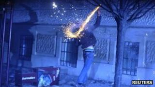 A protester throws a firework during demonstrations in Maribor, Slovenia, 3 December 2012