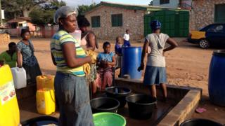 Women standing around a tap