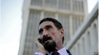 John McAfee speaks on his mobile phone in front of the Supreme Court in Guatemala City on December 04