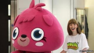 A sales assistant walks the Moshi Monster 'Poppet' to a pop-up shop selling merchandise from the children's online game 'Moshi Monsters'