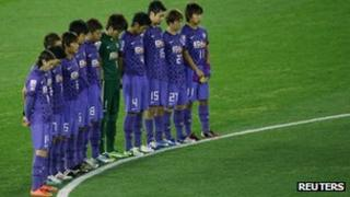 Players of the Japanese team Sanfrecce Hiroshima observe a minute's silence at football's Club World Cup on Thursday