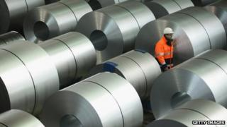 Man wanders among rolls of steel