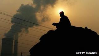 A sits near a power plant emitting plumes of smoke in Beijing, China. File photo
