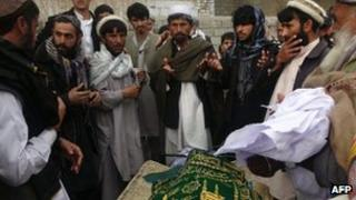 "Afghan men pray during the funeral of Najia Sidiqi, the acting director of the women""s affairs department in Mihtarlam on December 10, 2012"