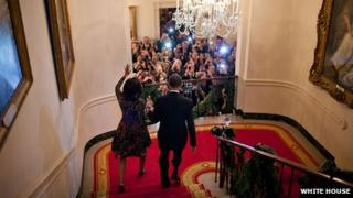 First Lady Michelle Obama and President Barack Obama descend the stairs to a December 2009 White House Christmas celebration