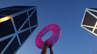 A protester holds a life saver in front of a bank in Madrid. Photo: June 2012