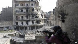 a Free Syrian Army fighter is in position in front of destroyed buildings in Aleppo, Syria on 29 November