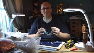 Paul Mason holds a handmade necklace