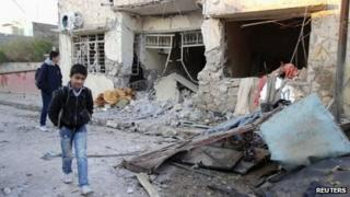 Boys walk past the scene of a bomb blast in Tuz Khurmatu, Iraq (17 December 2012)