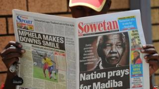 A man reads a local newspaper bearing in the headline a photo of former South African President Nelson Mandela, in Soweto on 10 December 2012 in Soweto