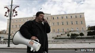 A Greek public sector worker outside the country's parliament, protesting about spending cuts