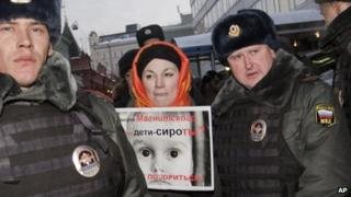 A Russian protester against a ban on US adoption is detained by police in Moscow