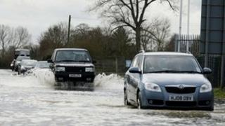 People drive along a flooded road near Melksham in Wiltshire