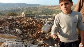 A boy holds up a piece of what rebel fighters said was the remains of a Scud-type missile that landed near the Sheikh Suleiman airbase near Darat Izza in northern Syria (13 December 2012)