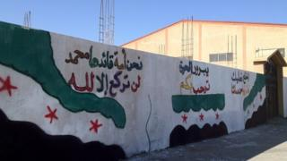 "Slogans from left to right decorated with rebel flag: ""We're a nation whose leader is Mohamed and won't bow to other than Allah"", ""Free Yabrood welcome you"" ""Take off your shoes as Yabroud's sand is (made up of) our blood"""