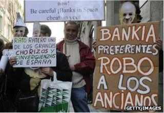 """People hold placards reading """"Bankia steal elderly people"""" and """"Rato thief"""" during a demonstration against Bankia and former IMF chief Rodrigo Rato in front of Spain""""s National Court in Madrid"""