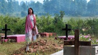 A 60-year-old Anglo-Indian resident of McCluskieganj, in eastern India, walks through a Christian cemetery in October 2011.