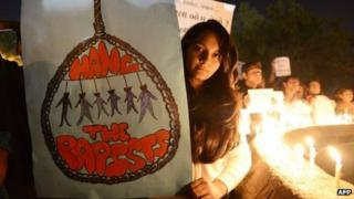 Protesters hold candles and posters during a rally in Ahmedabad on December 30, 2012