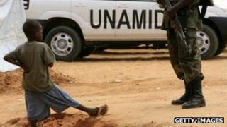 A boy plays beside a UN peacekeeper in Darfur, Sudan (file image)