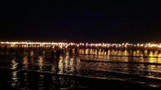Torchbearers walk into Weymouth Bay