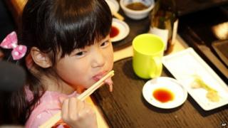 Girl eats bluefin tuna sushi