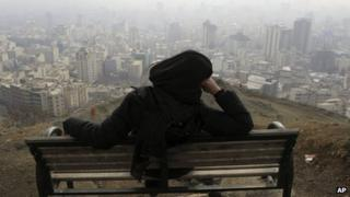 Iranian woman looks on at the smog covering Tehran, Iran, on 4/1/13