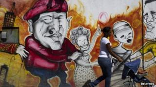 Woman walks past a mural of Hugo Chavez