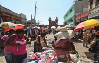 A woman at a stall with the Iron Market in the distance