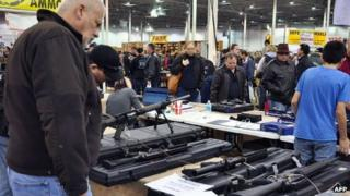 "Gun show goers look at various assault-style weapons December 30, 2012 at the Nation""s Gun Show in Chantilly, Virginia"