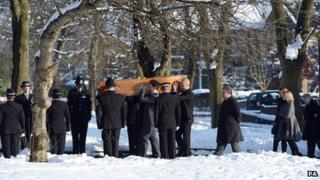 Police officers stand in a row as coffin is carried