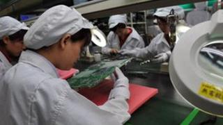 factory workers examine motherboards