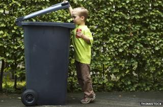 Boy putting a can in a bin
