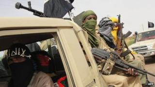 A picture taken on 7 August 2012 shows fighters of the Ansar Dine Islamist group standing guard at Kidal airport, northern Mali