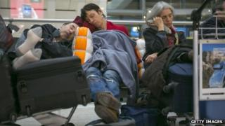 Passengers asleep in a departure lounge at London Heathrow
