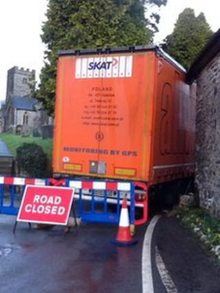 Lorry wedged between churchyard and house in Brompton Regis