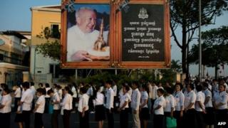 Thousands of Cambodians queue to enter the crematorium area where the coffin of late King Norodom Sihanouk (pictured on portrait) rests before his cremation near the Royal Palace in Phnom Penh on 4 February 2013