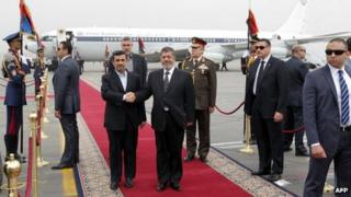 Mahmoud Ahmadinejad (L) and Mohammed Morsi (R) stand together at Cairo International Airport (5 February 2013)