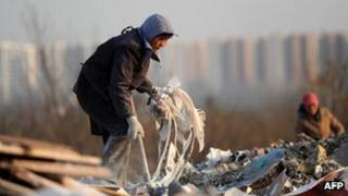 A Chinese resident going through a waste dump