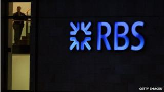 RBS employee looks out from the headquarters building next to a neon sign