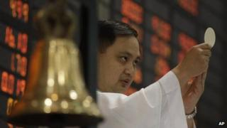 A catholic priest blesses the Philippines stock exchange in Manila