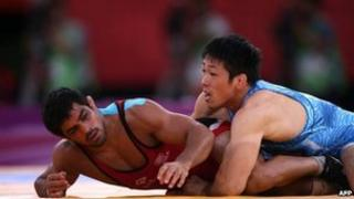 """India's Sushil Kumar (L) wrestles Japan""""s Tatsuhiro Yonemitsu in their Men's 66kg Freestyle gold medal match on August 12, 2012 during the wrestling event of the London 2012 Olympic Games"""