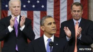 US House Speaker John Boehner (R-OH) and Vice President Joe Biden (L) stand to applaud as President Barack Obama delivers his State of the Union speech