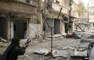 An opposition fighter uses a catapult to launch a handmade grenade in Aleppo, Syria, 12 February