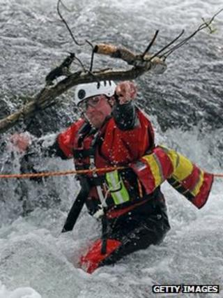 A member of a mountain rescue team moves a branch that has been caught on fast-flowing river water as they help in the search for April Jones